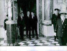 Portrait of a Finnish writer and President of Finland Urho Kaleva Kekkonen walking with men and coming out from the building. 1967