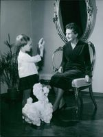 Portrait of a Finnish writer and President of Finland Sylvia Salome Kekkonen siting and talking with child.