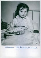 A photo of a foundling child sitting in a bed eating at an orphanage.