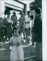Soldiers and people standing while the child looking in Lebanon.