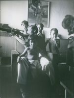Nguyễn Cao Kỳ pointing a rifle gun with his children around him.