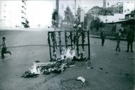 A photo of a burning material in the street of Lebanon while children at their young age looking at it, happened during Cairo Agreement effect.