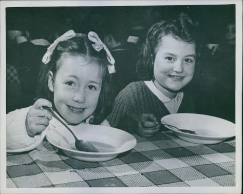 Two Italian cute little girl are smiling when taking meal provided by Military government of US as a part of the Free Food Campaign during World War II
