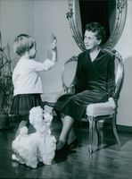 Sylvi Uino Kekkonen being entertained by a little girl with her little toys.