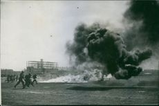 War Damages. 1939 View of a bomb blast, soldiers running towards it to extinguishes the fire.