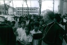 Man standing in street with little children and talking to them.