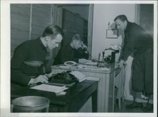 An office with three men getting busy in Finland publishing war related news.
