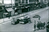 Soldiers gathered in street  and having discussion with the drivers of cars.