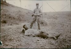 A soldier lying down in the ground while the other one holding a sword during Russo-Japanese War, 1904.