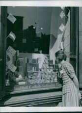 A Dutch housewife inspects stocks of Allied relief food in the window of a shop selected as a distribution centre in Utrecht, Holland, 1945.