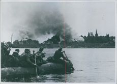 Soldiers crossing the river and looking at the smoke puff Netherlands during WWII, 1940.