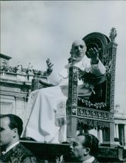 Pope Pius XII is siting on a gestatorial chair during a ceremony.