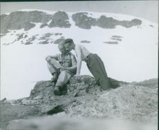 A man sitting on rock and reading a letter, another man standing beside looking at him in Norway 1940.