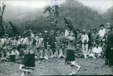 A rifle is held high, young girls dancing for Laotian troops in a Sam Neua province training group.