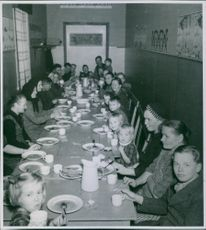 A photo of people during mealtime. 1945