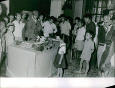 Children gathered around a table and looking at the weapons on the table.