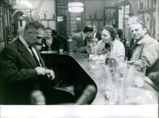 1961 Marie Besnard in a bar counter with people around.