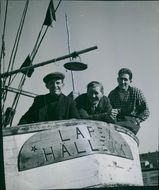 Three man facing camera and standing on a boat. 1950.Three man standing on a boat.