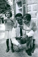 1966 Portrait of a man with children, one of them is looking something the other is holding a picture.