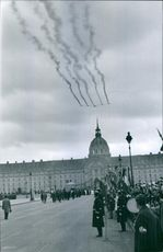Airplanes flying in sky during an event in street.