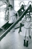 Girl swinging on swing, while another girl wearing tiger mask.1966