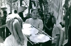 A Vietnamese woman holding sun-dried goods.  - May 1965