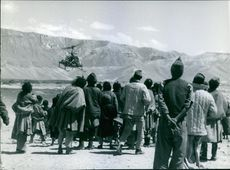 Villagers gathered to see a helicopter.