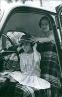 Two children siting inside the car, wearing hat.1966