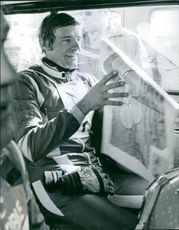 Jean-Claude Killy reading paper sitting in a car.