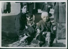 An Italian mother and two small children sitting on a curb in Naples.