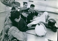 German Air fighter pilots standing together  looking at the map.