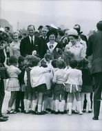 Elizabeth II standing with Prince Philip taking flowers from children.