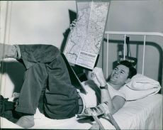 A patient named Earl McCarthy lying on the bed with a map of Western Germany o his hands.