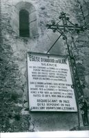 A crucifix and a sign board on the wall outside the church, in Oradour-sur-Glane, 1971.