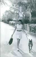 Woman walking with a dog and holding a bag, 1971, the time of war crimes being investigated.