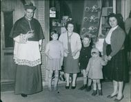 A bishop standing with women and children.