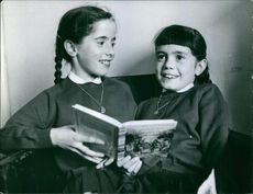 Two young girls are holding a book. 1972