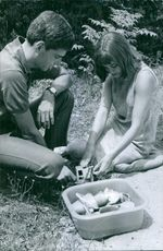 Man and woman playing with children's toys.  - Jun 1964