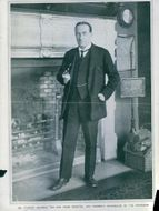 Stanley Baldwin standing by the fireplace.