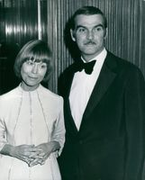 Stanley Baker with a woman while standing.