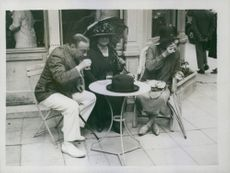 Stanley Baldwin and Lucy Baldwin drinking outside a restaurant.