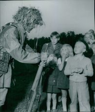 Soldier standing and talking to the children standing next to him.
