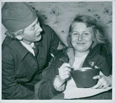 A woman taking care the girl while eating a meal in the Pubic shelters in Stockholm, 1955.