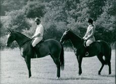 A royal photo of Prince Michael of Kent and Princess Michael of Kent in their classic riding outfits and relaxed stances in the grounds of Mayfield House estate in Susseex.