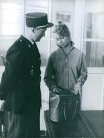 A guard checking the handbag of Marion Michael.
