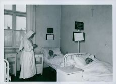 A nun standing beside of the wounded soldiers in the bed during Soviet invasion of Poland.