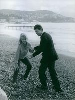 Marion Michael playing with a man on a beach.