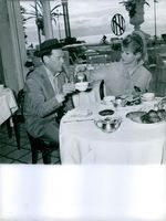 Marion Michael serving a tea to a man.