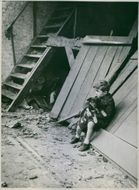 Child in front of destroy house.