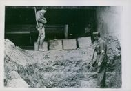 Members of the French Forces of the Interior examine the reopened graves